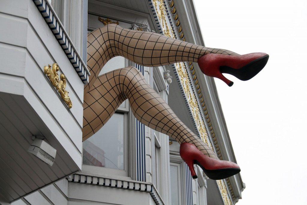 Grauen verschnörkelte Hausfassade. Aus dem Fenster ragen zwei Frauenbeine mit karierten Seidenstrumpfhosen.