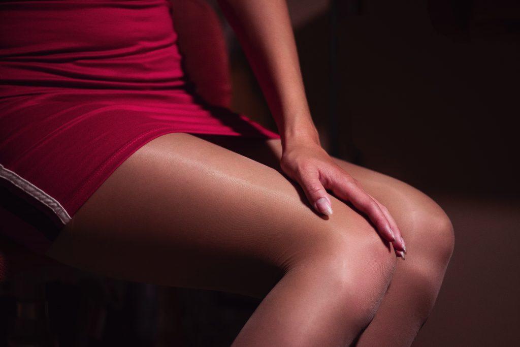 Oberschenkel von Frau sichbar mit rotem Kleid und zart schimmernden Seidenstrumpfhosen