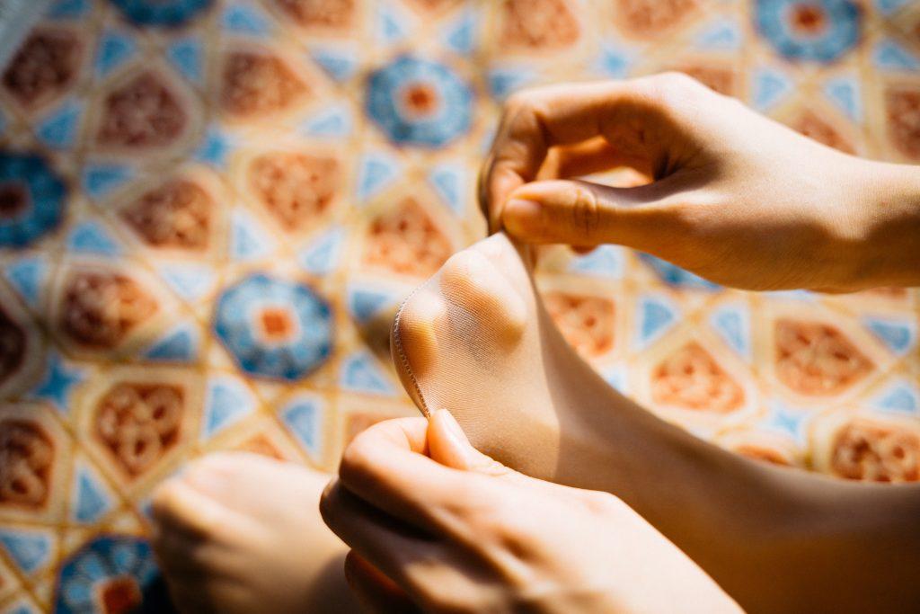 Fuß mit Seidenstrumpf und zwei Hände, die diesen gerad von den Zehen wegziehen.